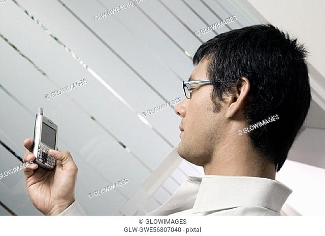 Side profile of a businessman holding a mobile phone