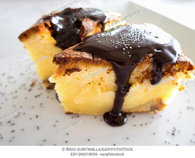 two pieces of cream cake with chocolate sauce on white dish