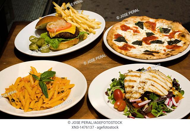 Roast meat with salad, Pasta, Pizza, Cheeseburger and Fries, on Plates. Soho, New York City, USA
