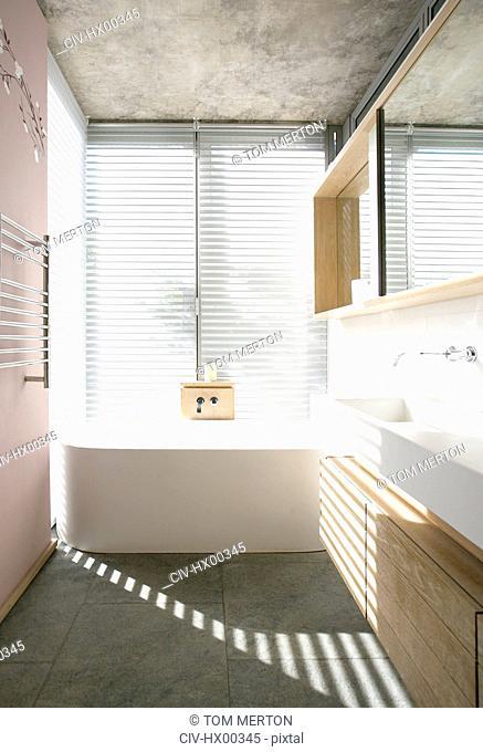 Light through blinds behind soaking tub in modern bathroom