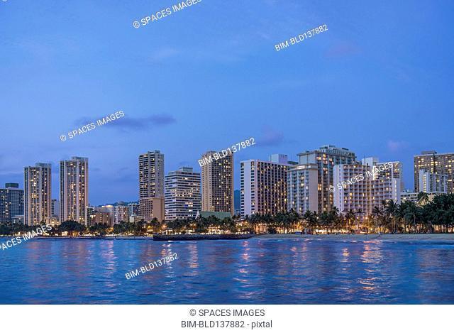 Illuminated city skyline on waterfront, Honolulu, Hawaii, United States