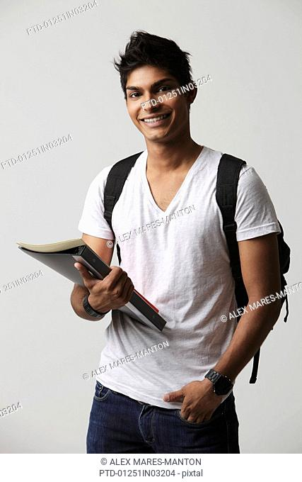 young man holding books and wearing backpack
