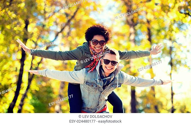 friendship, leisure, international, season and people concept - happy teenage couple in shades having fun over autumn park background