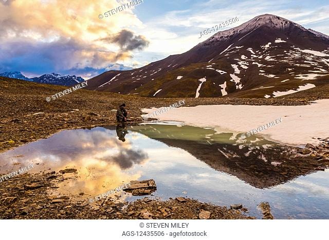 A backpacker pauses for rest beside a puddle while crossing over an unnamed pass in the Brooks Range under the midnight sun at 12:14 a.m