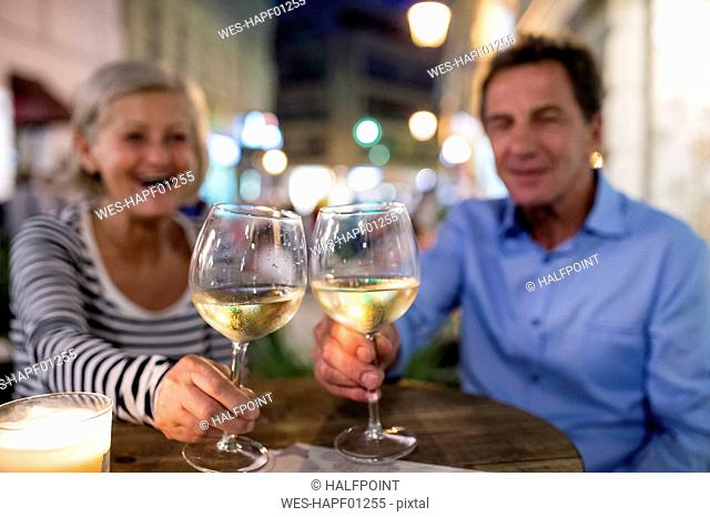 Senior couple drinking wine at an outdoor bar