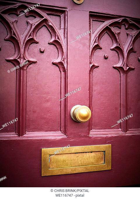 Detail of a red Victorian door with copper or brass letterbox in Manchester, UK
