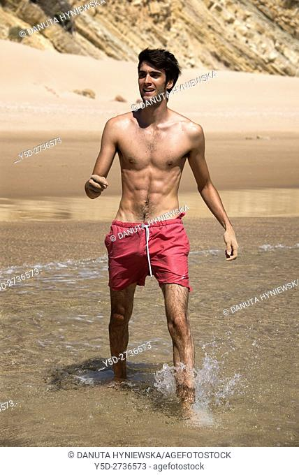young man on vacation on the beach, here Salema beach, Vila do Bispo, Algarve, Portugal, Europe