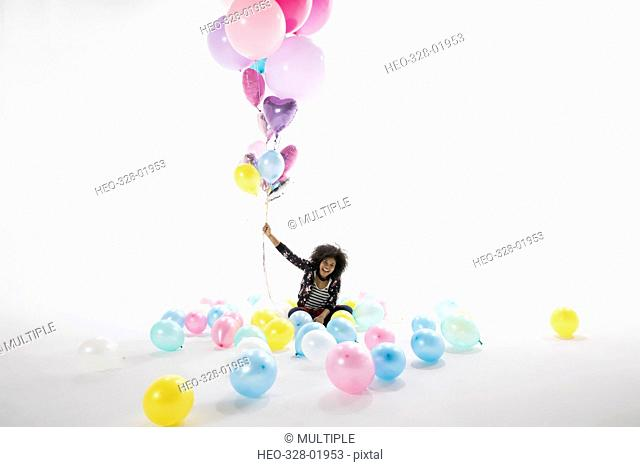 Portrait smiling young woman holding bunch of multicolor balloons against white background