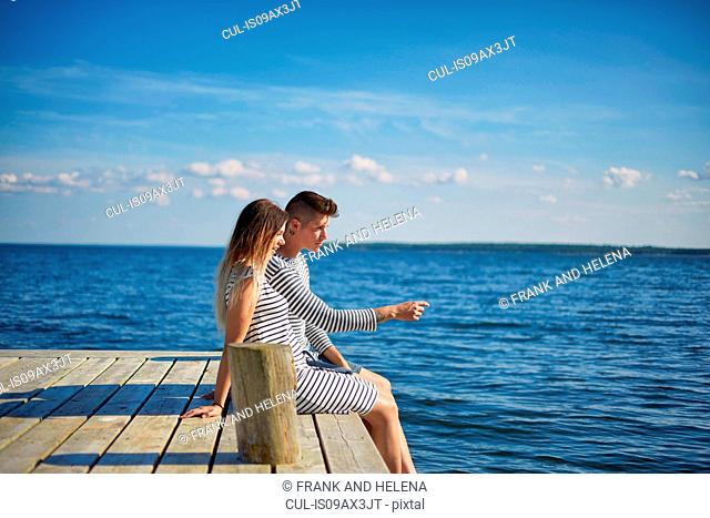 Couple sitting on wooden pier, looking at view