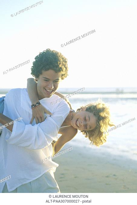 Girl hanging on boy's back on beach