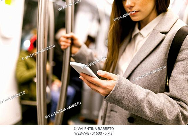 Businesswoman using cell phone in underground train, partial view
