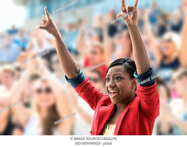 Excited woman in crowd, making hand gesture