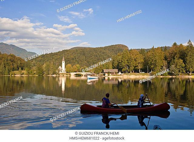 Slovenia, Goriska Region, Bovec, the Triglav National Park, canoeing on the Bohinj lake and St John the Baptist church in the background