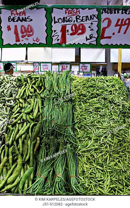 Faya beans and long green beans in grocery store display, price signs, Devon Avenue, multiethnic shopping district. Chicago. Illinois, USA