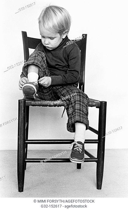 Little boy tying shoelace