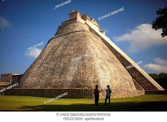 A guide speaks with a tourist in front of the Pyramid of the Magician or the Temple of the Magician in the Mayan city of Uxmal, Yucatan Peninsula, Mexico