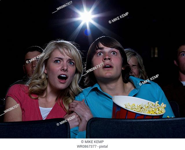 Boy and girl with popcorn frightened at movie theater
