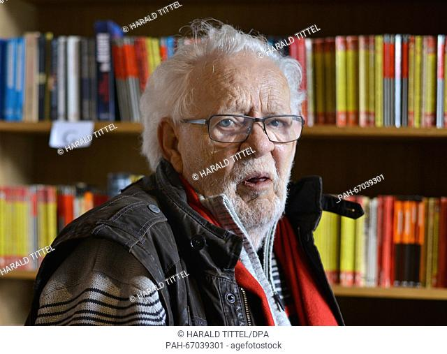 Crime writer Jacques Berndorf poses in front of a bookcase during a press conference for his 80th birthday, at Cafe Sherlock in Hillesheim, Germany