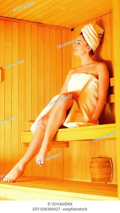 Spa beauty treatment and relaxation concept. Woman white towel relaxing in wooden sauna room