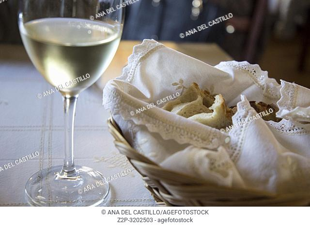 White wine and basket of bread on table in restaurant Azores Portugal