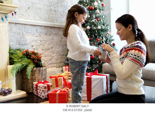 Mother and daughter opening Christmas gift in living room