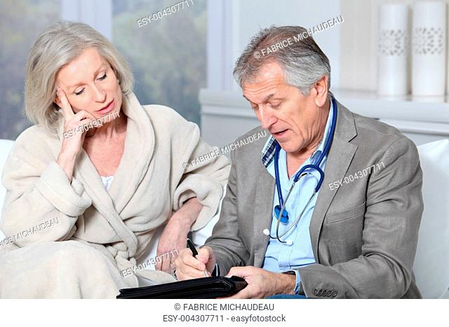 Doctor writing prescription to patient