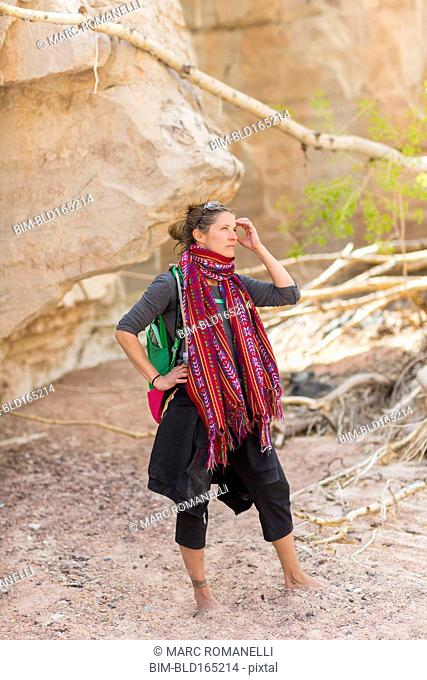 Mixed race hiker exploring desert rock formations barefoot