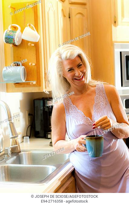 A 52 year old blond woman smiling at the camera and holding a cup of tea in a kitchen
