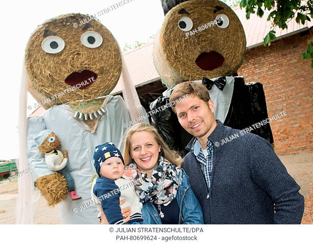 "Farmers Harm Wilhelm and Jennifer Ahlwes and their six-month-old son Jannes Wilhelm against """"their"""" straw figures in the Hanover region, Germany, 26 May 2016"