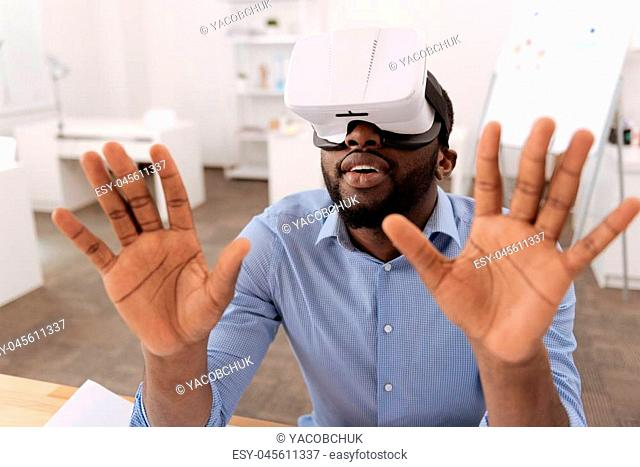 Future technologies. Serious nice pleasant man wearing 3d glasses and looking at the virtual screen while pressing his hands to it