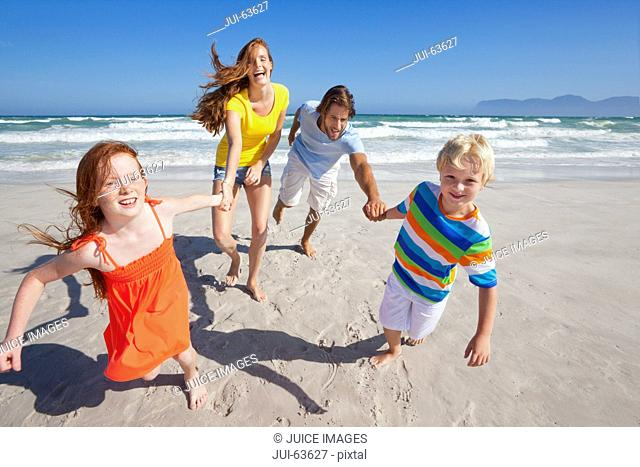 Happy family smiling at camera, holding hands, on sunny beach