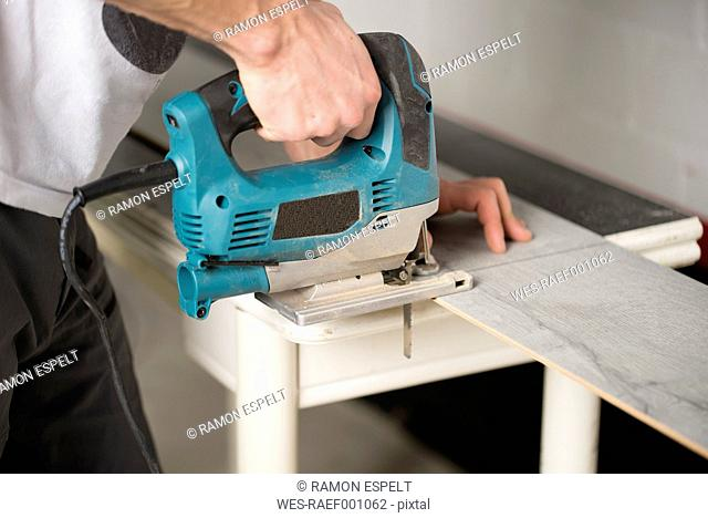 Man cutting laminate floor pieces with a jigsaw