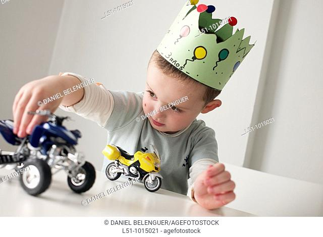 Boy with a crown in his birthday playing with cars on a table