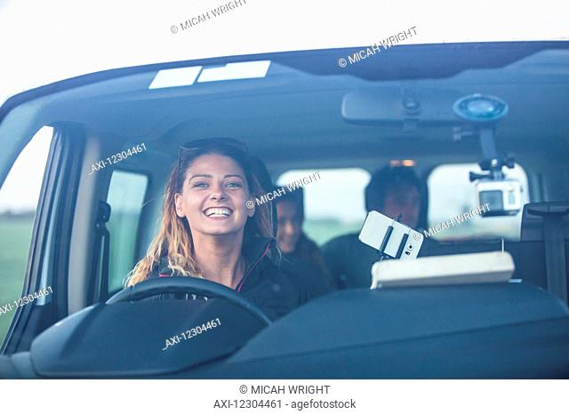 A young woman smiles from the driver's seat of a vehicle while looking through the windshield; Egmond aan Zee, Holland
