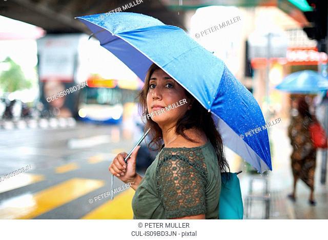Tourist waiting to cross street, Kuala Lumpur, Malaysia