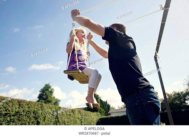 Low angle view of playful father with daughter on swing in back yard against sky