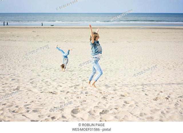 Mother and daughter having fun, cartwheeling on the beach