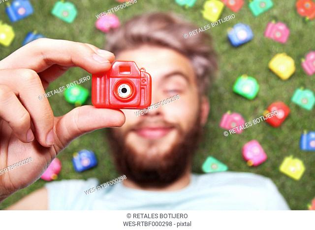 Young man holding toy camera