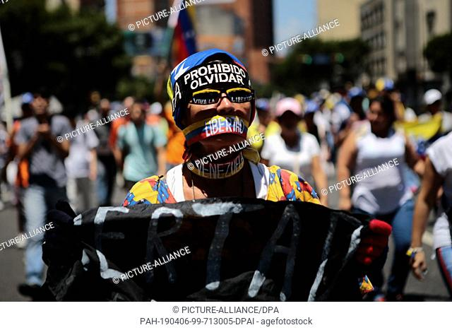 "06 April 2019, Venezuela, Caracas: A woman in a cap with the slogan """"Prohibido Olvidar"""" (Forgetting is forbidden) walks on the street during a protest rally..."