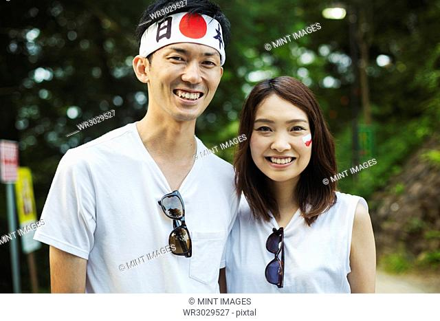 Portrait of man wearing headband and young woman with brown hair, Japanese flag painted on her cheek, smiling at camera