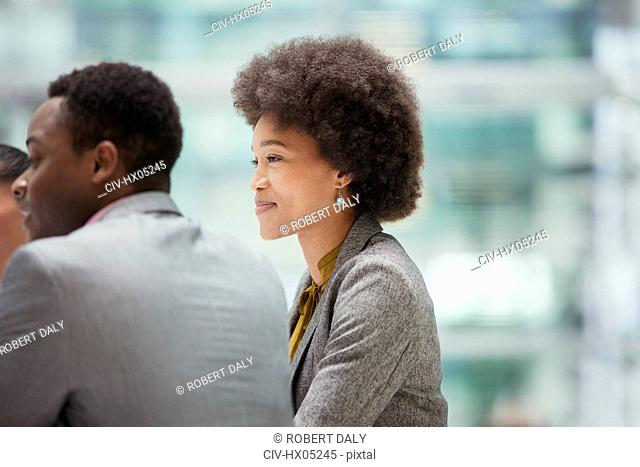 Smiling, confident businesswoman listening in meeting