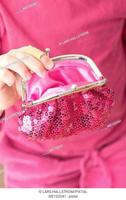 Hand of little girl holding pink change purse