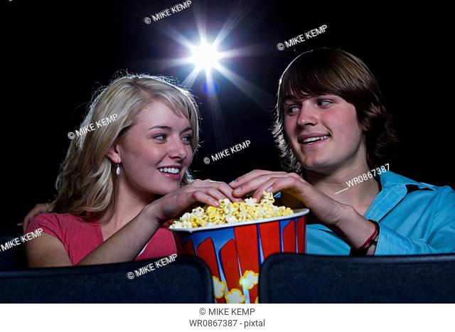 Boy and girl touching hands in popcorn at movie theater