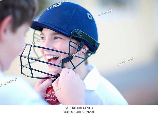 Boy putting cricket helmet on another boy