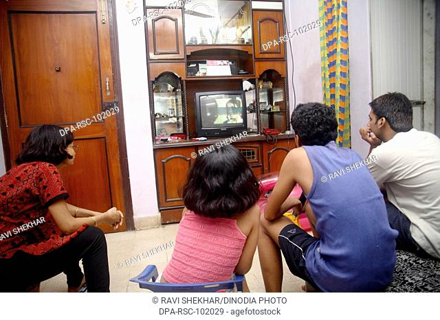 Indian family watching TV , urban space , Middle class , Mira Road suburb of Bombay Mumbai ,  Maharashtra , India , Model released 542