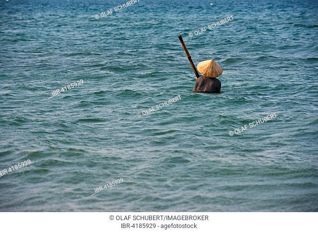 Mussel hunter wearing a straw hat, shellfish fisherman on Cua Dai beach in Hoi An, Vietnam