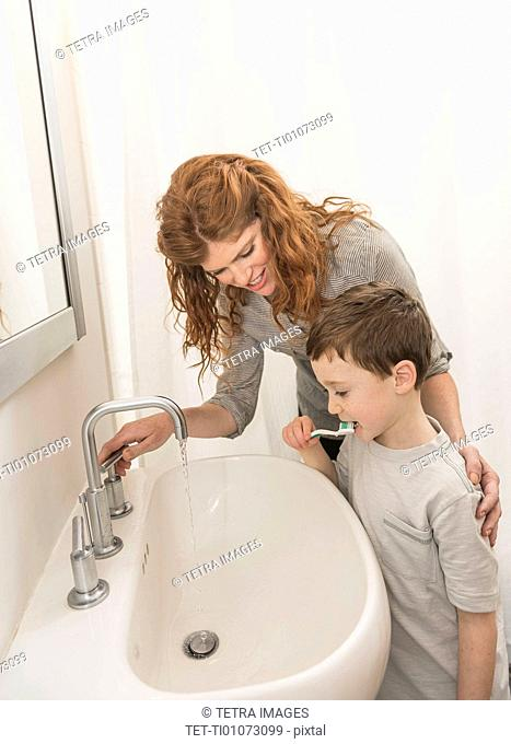 son (6-7) and mother brushing teeth