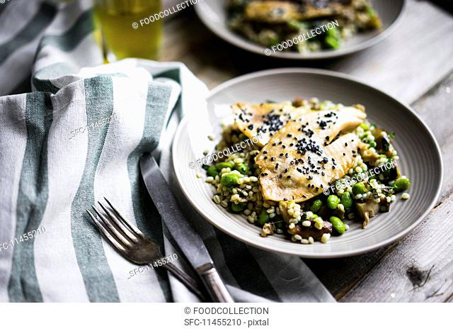 Grilled fish fillet with mushroom risotto and edamame beans on a rustic surface