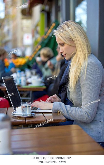 Pretty blonde woman with laptop in a Cafe