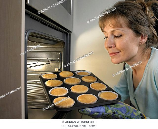 Woman baking cupcakes in kitchen